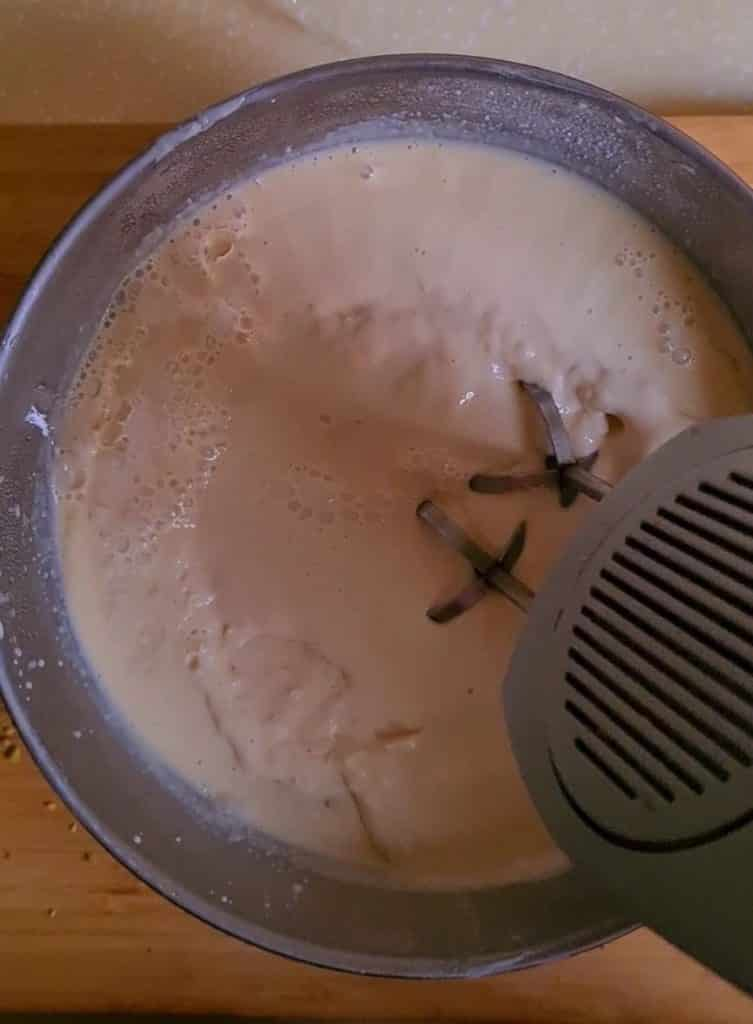 beating the semi frozen kulfi base with an electric beater