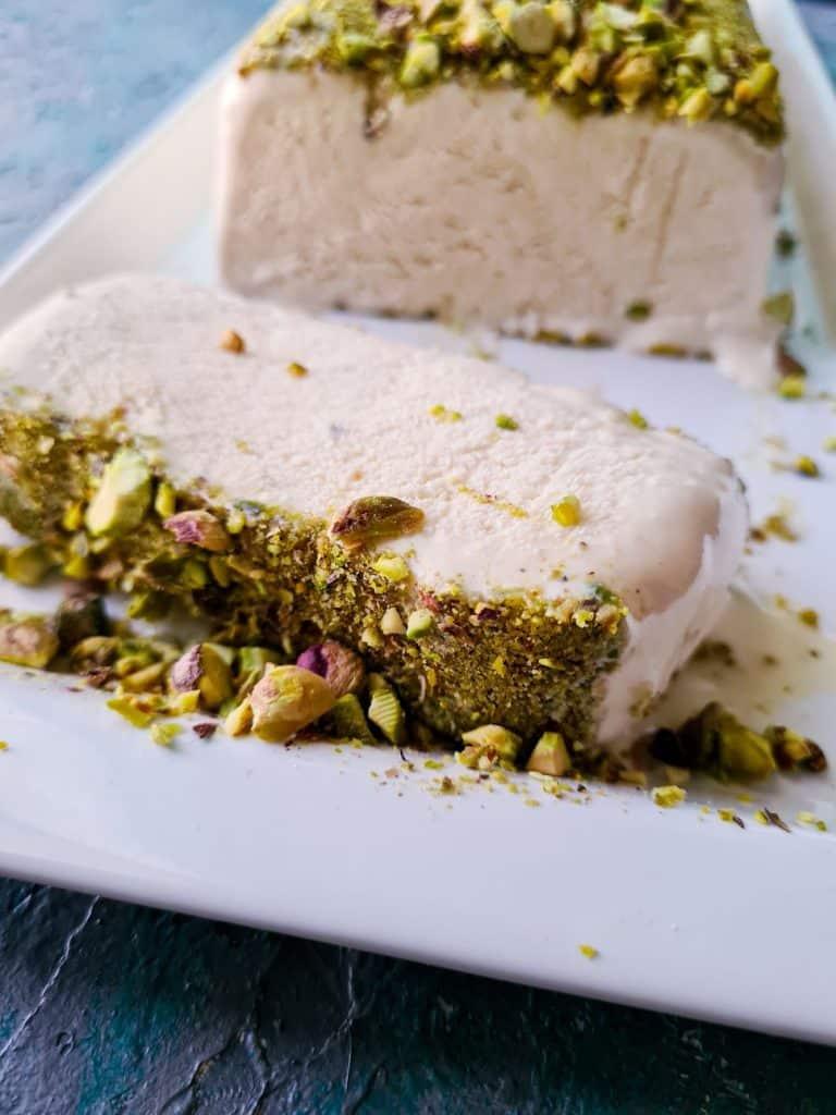a slice of malai kulfi cut from the main bar fallen on a white dish
