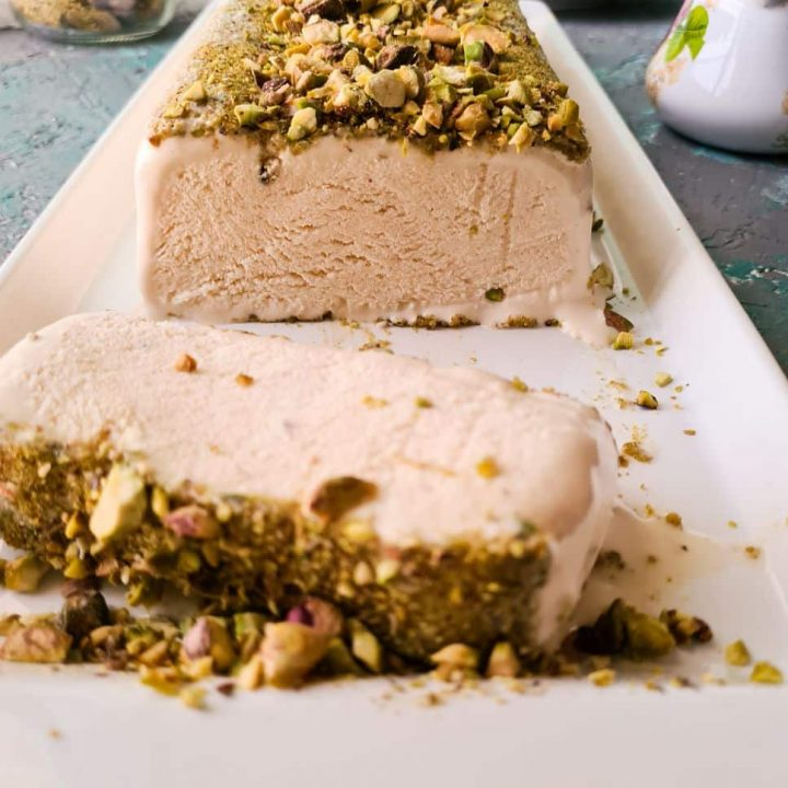 a slice of kulfi in a white dish topped with chopped pistachios