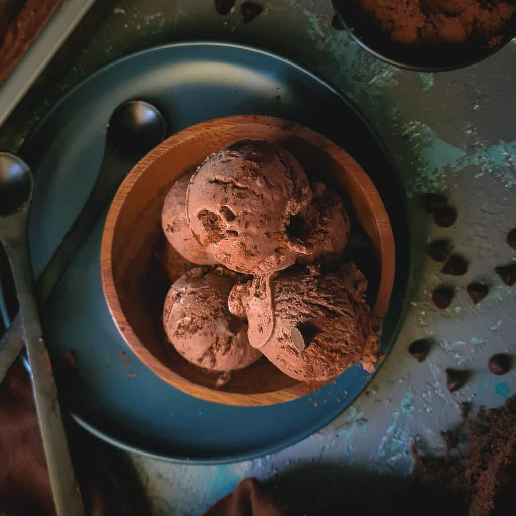 4 scoops of chocolate ice cream in a wooden bowl with a few chocolate chips scattered around