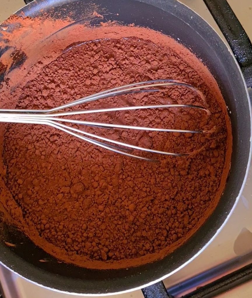 cocoa powder and milk in a pot along with other ingredients