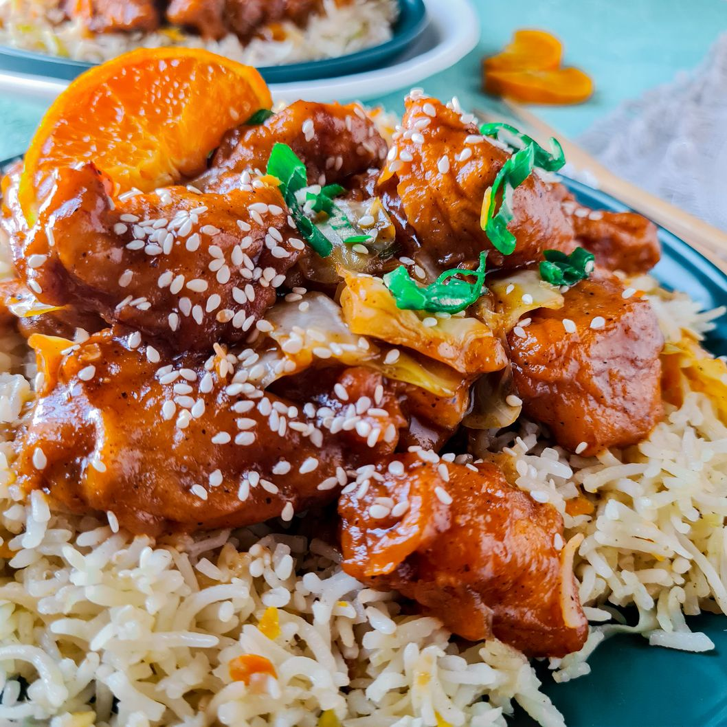 orange chicken with sesame seeds on top of a bed of rice
