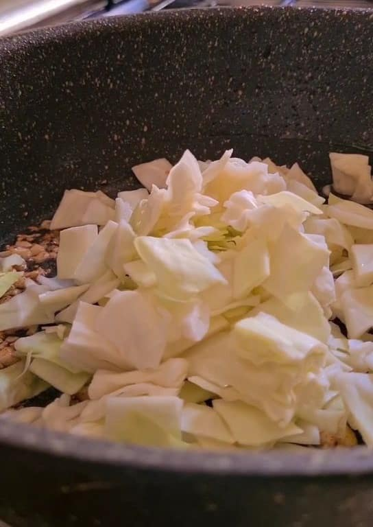 chopped cabbage in black pan