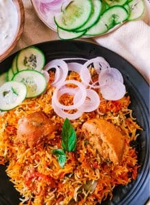 a plate of chicken pieces and colored rice with some onion and cucumber sliced on the side
