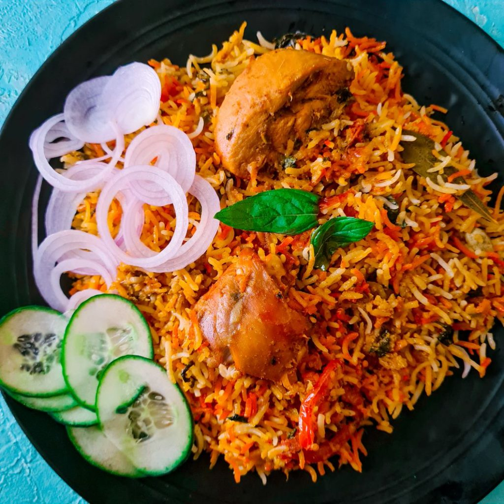 a plate with orange red and white spicy rice with 2 pieces of chicken on it and some sliced cucumber and onions on the side on a black plate