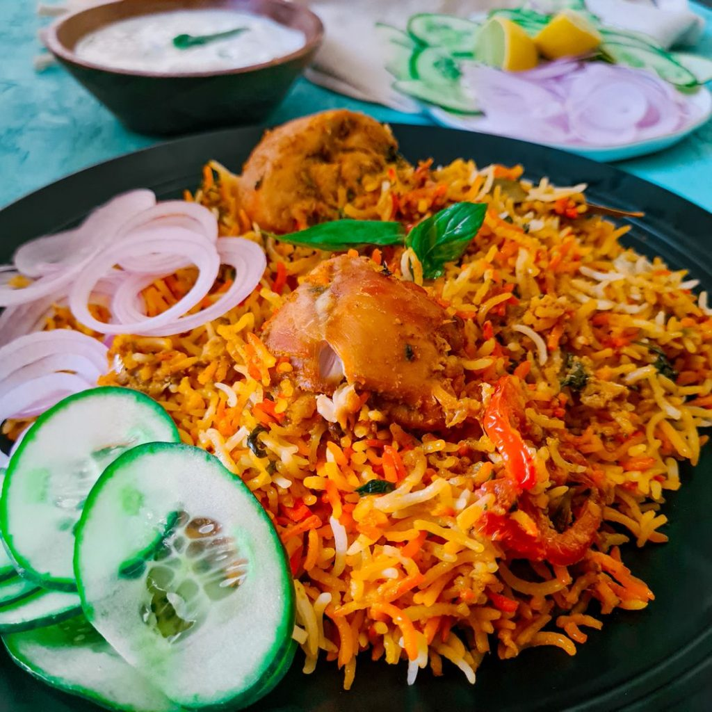 chicken biryani on a black plate with a side of sliced cucumber and onions