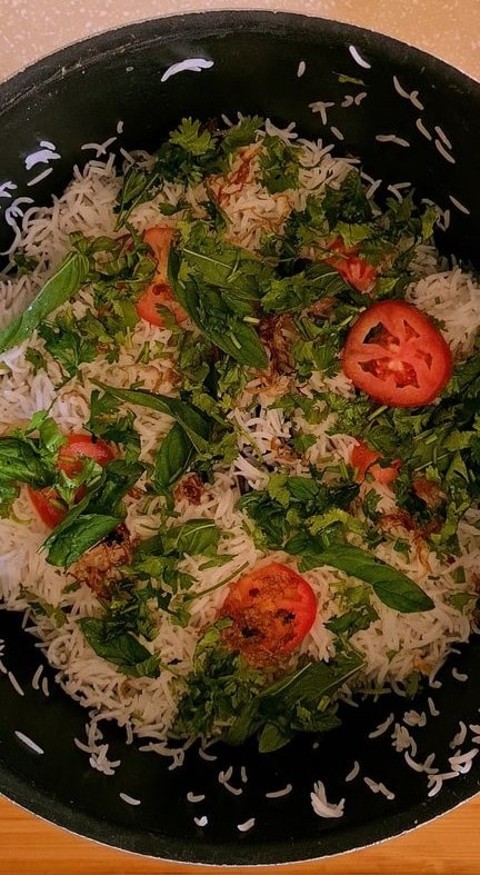 mint leaves and tomato slices added on top of a layer of rice