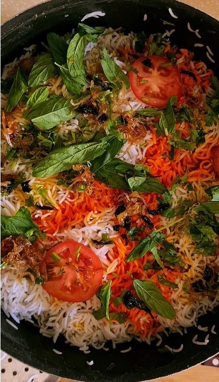 adding garnishes to the Chicken biryani