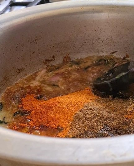 spices added to brown onions in a pot