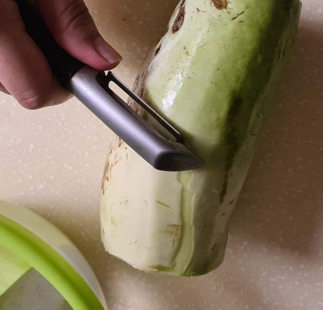 bottle gourd being peeled with a peeler