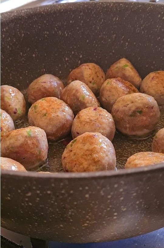 chicken meatballs in a wide saucepan being sauteed