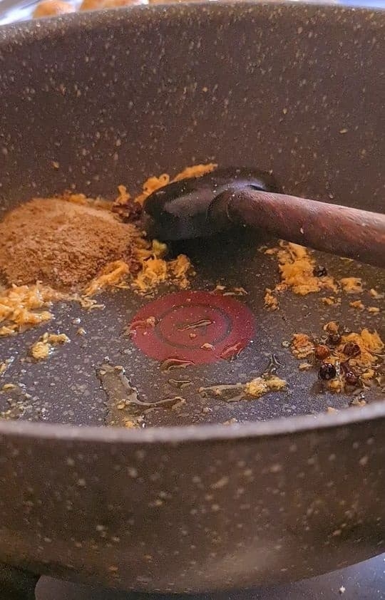 some spices, brown garlic and a wooden spoon in a saucepan