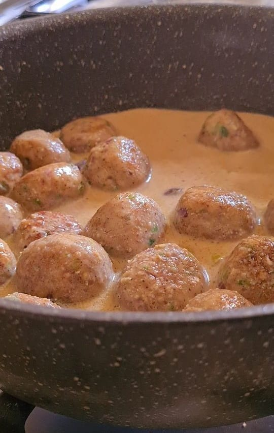 meatballs in a white sauce in black saucepan