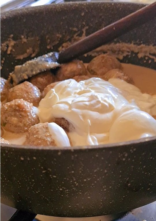 thick cream added to white sauce and meatballs