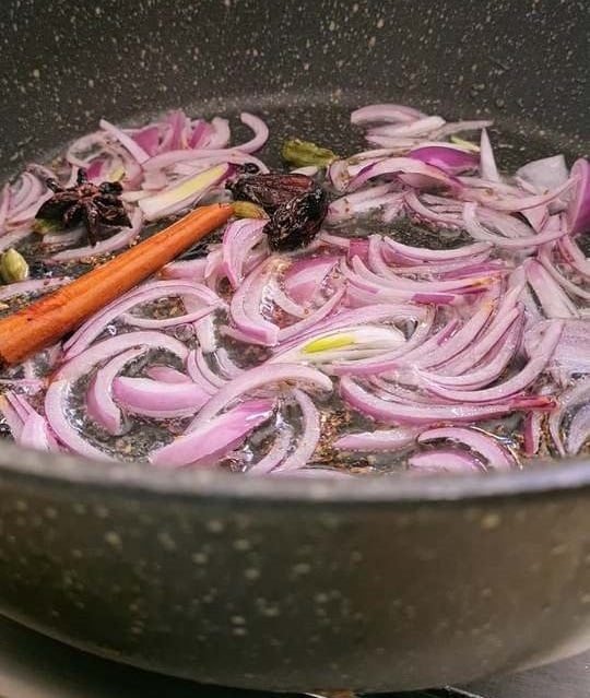 sliced onions in oil with whole spices