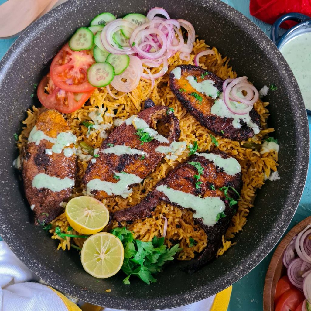 fish tehri in a black pot with raita and salad on the side