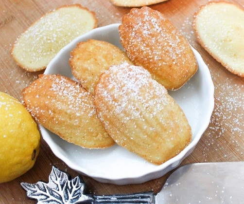 4 madeleines sponge cakes in a bowl with more scattered around them