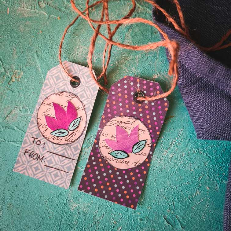 2 handmade gift tags on a blue surface