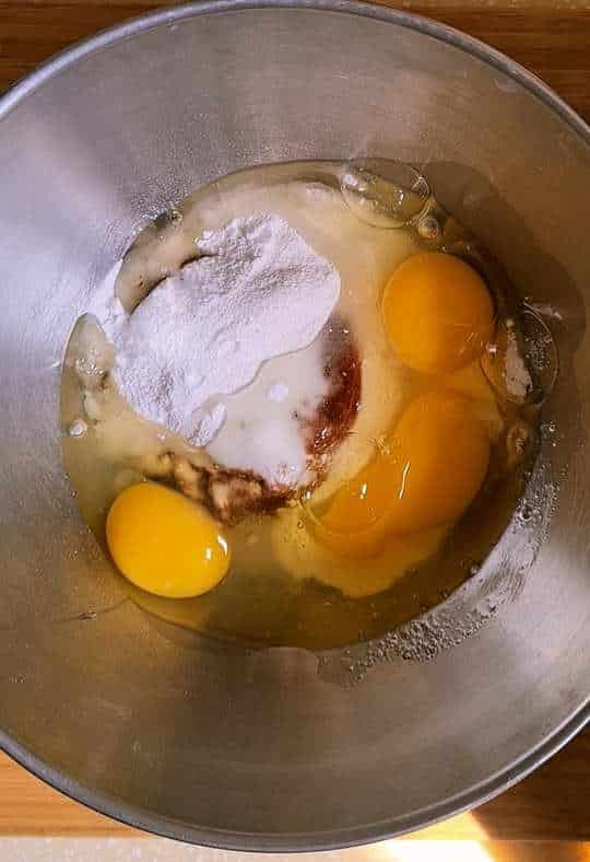 raw eggs and sugar in a steel bowl unmixed