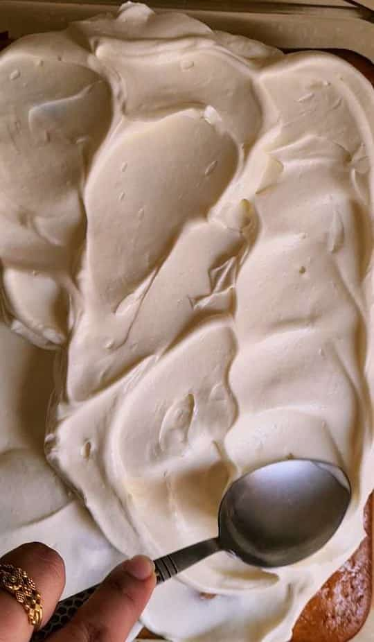 using a spoon to spread out whipping cream