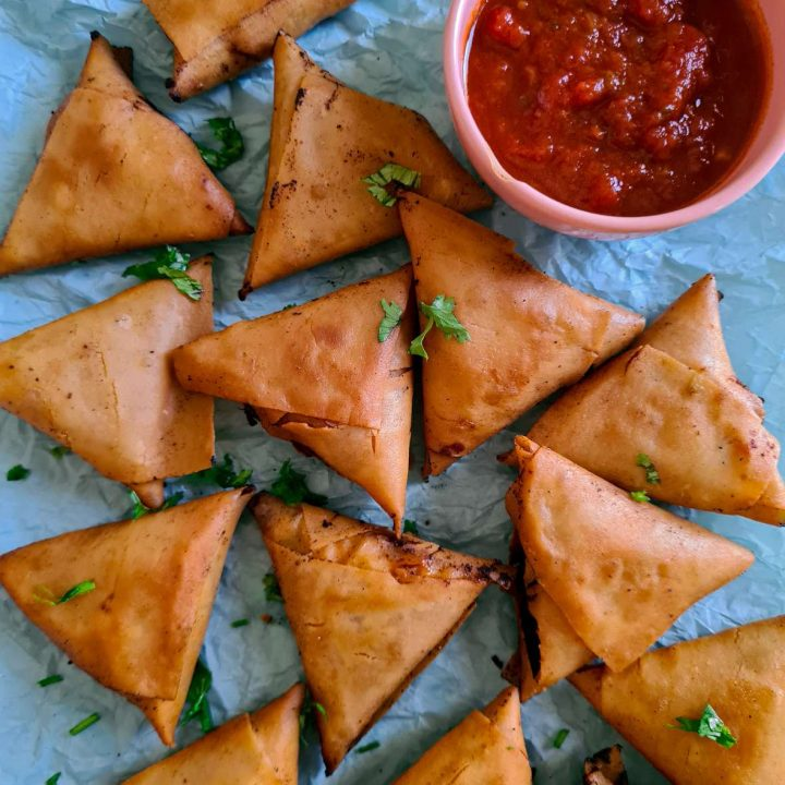 samosas laid on a blue paper with some ketchup on the side