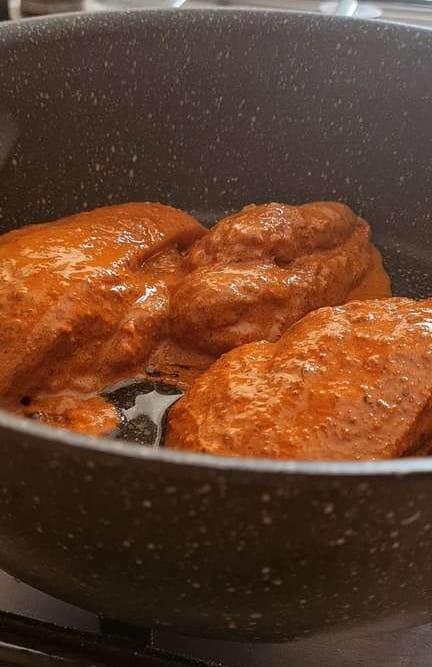 chicken fillets marinated in red tikka masala in a pot