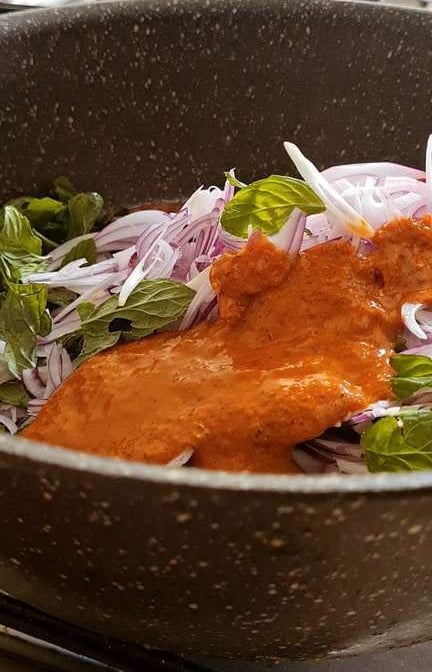 raw onions, mint leaves and tikka marinade in a pot