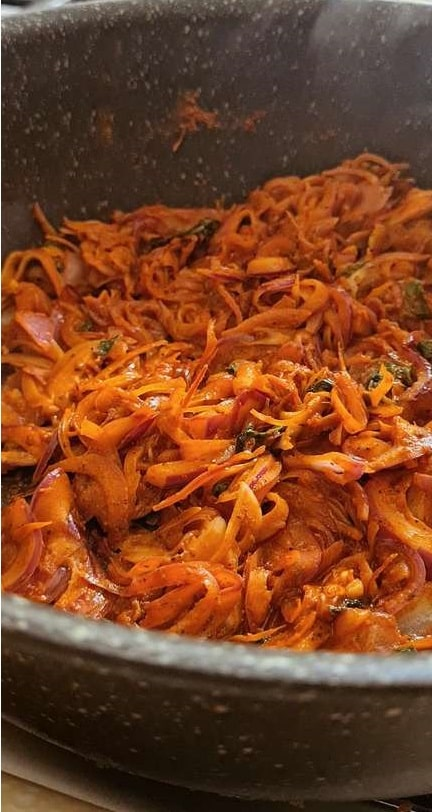 orangish red spicy onions cooked in a pot