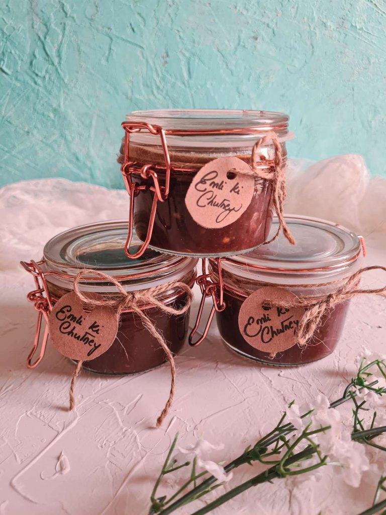 imli or tamarind chutney in 3 glass jars, one on top of the other two. all jars labelled with tags