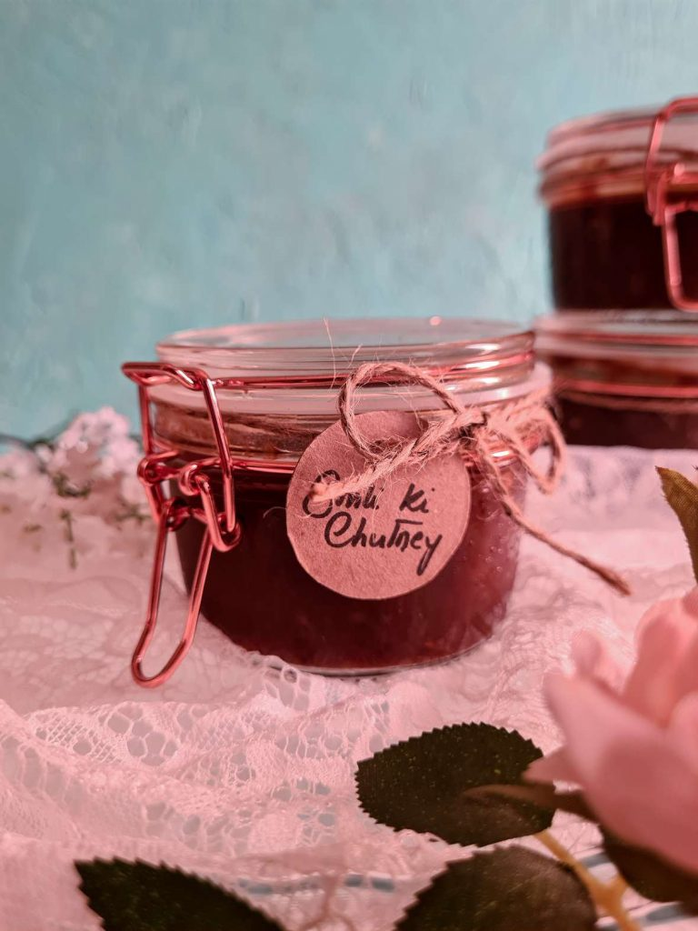 a small glass jar with imli ki chutney in it, labelled with a brown tag against a blue backdrop