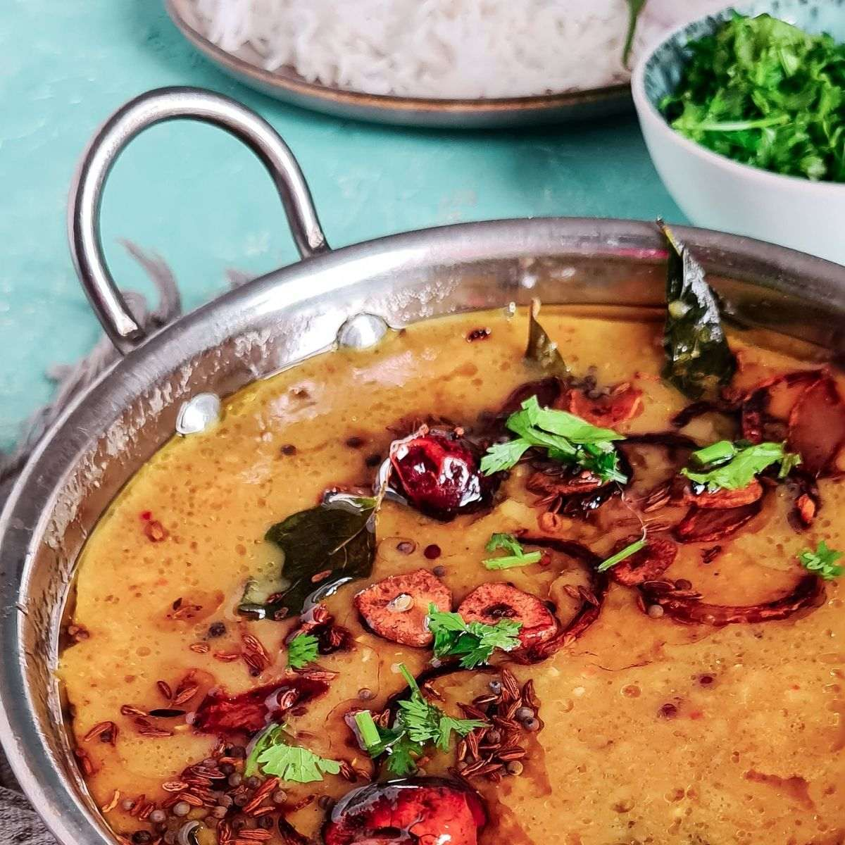 a view of khatti dal in a steel bowl with some rice and coriander show from the side.