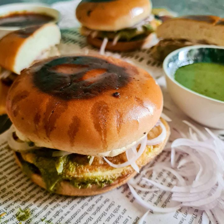 an assembled bun kebab in focus, with 2 in the background, a green chutney and sliced raw onions peaking from the side