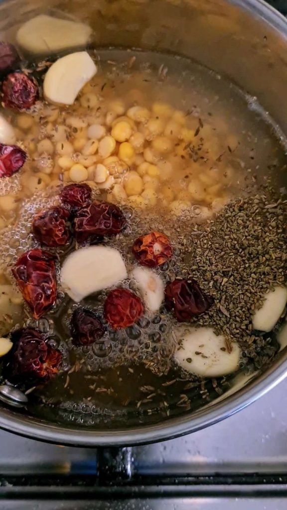 whole spices and split chickpeas submerged in water