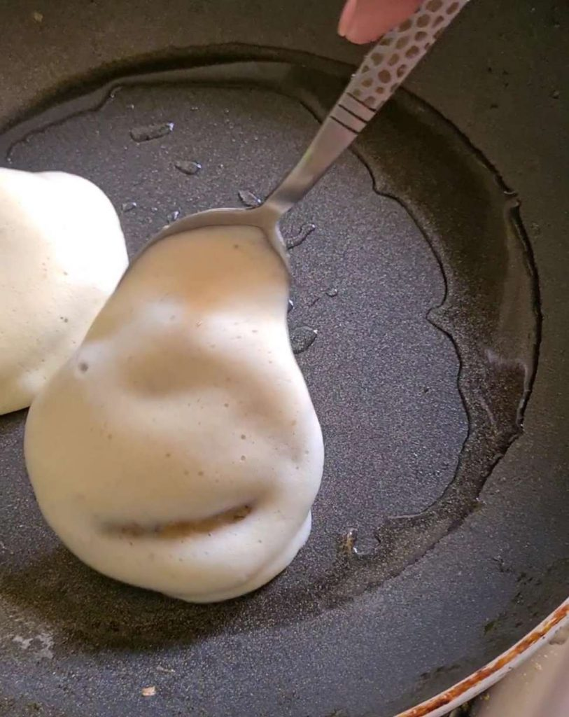 egg coated patties in a frying pan