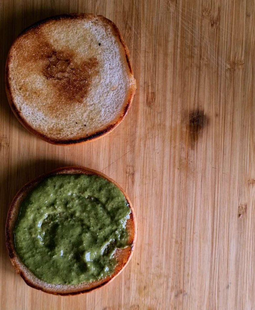 slathering green chutney on 2 toasted buns
