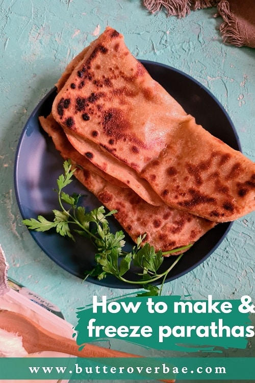 a folded square paratha or fried flatbread on a dark blue plate with some coriander on the side.