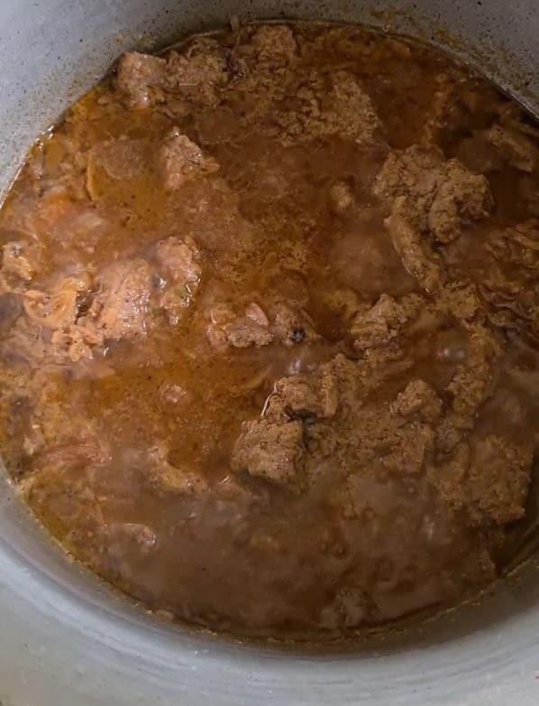boneless beef cubes cooking in a brown gravy