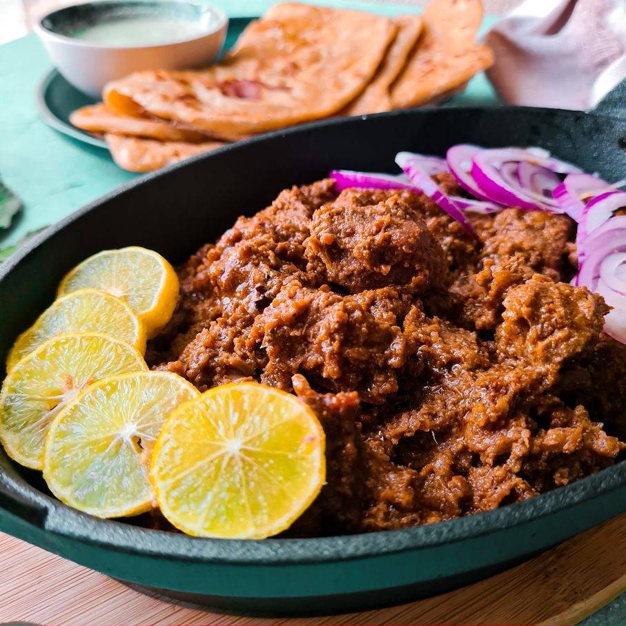 beef handi kababs in a oval cast iron platter with lemon and onion slices on top of it