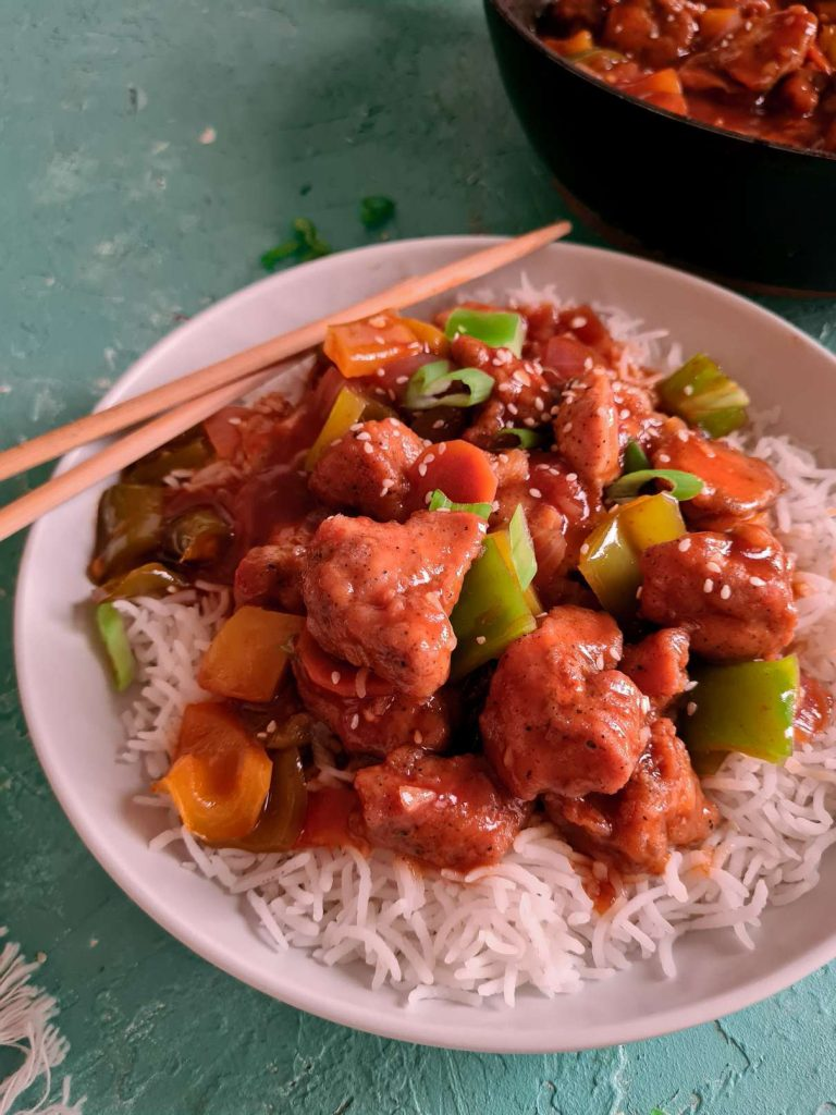 sweet and sour chicken on a bed of rice in a white plate with chopsticks on the side.