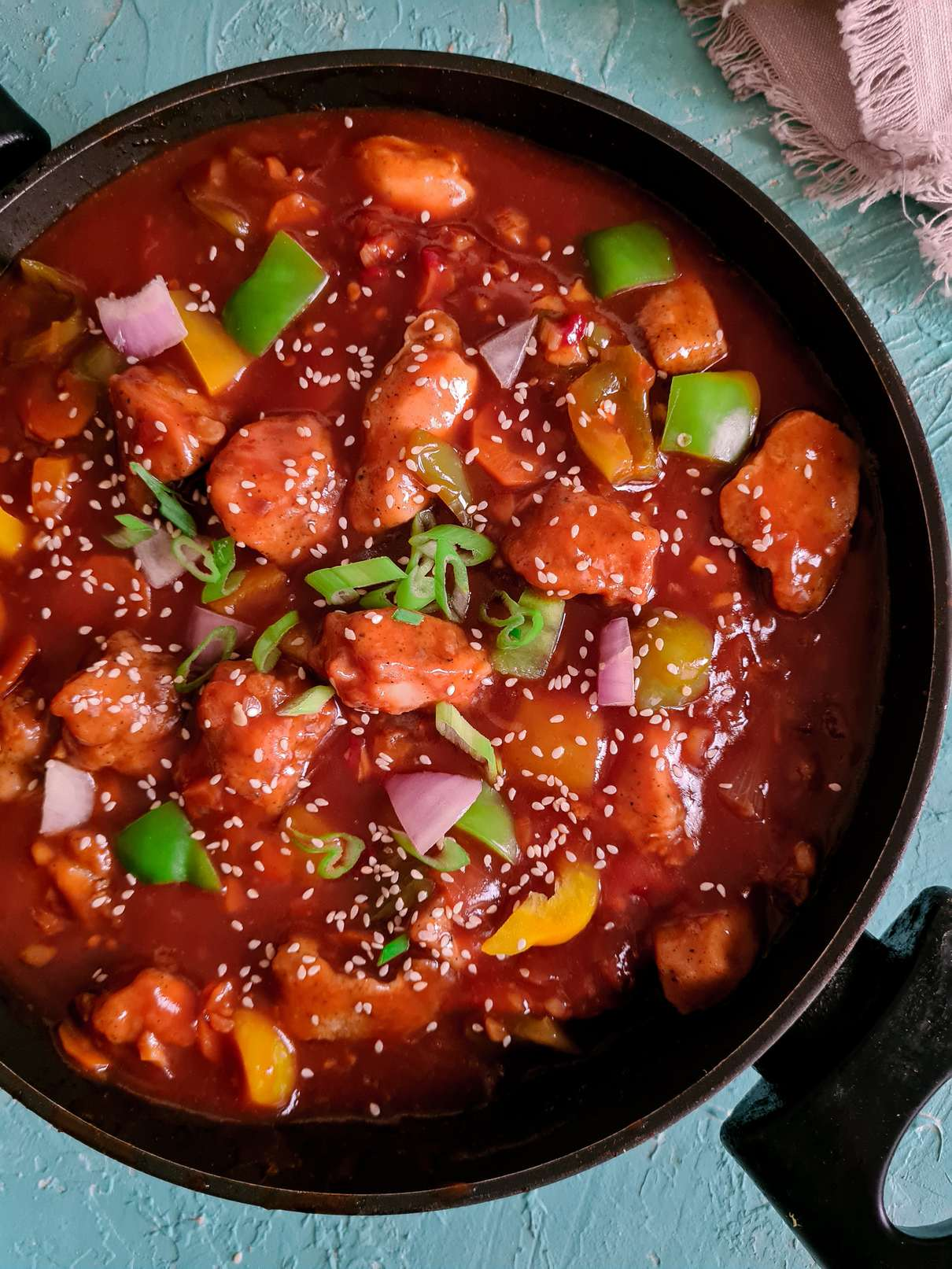 sweet and sour chicken with gravy in a black wok