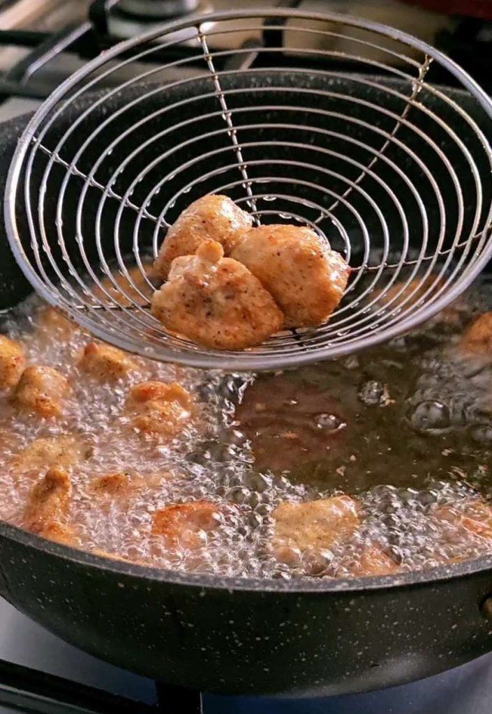 using a skimmer to remove fried chicken pieces from deep frying behind