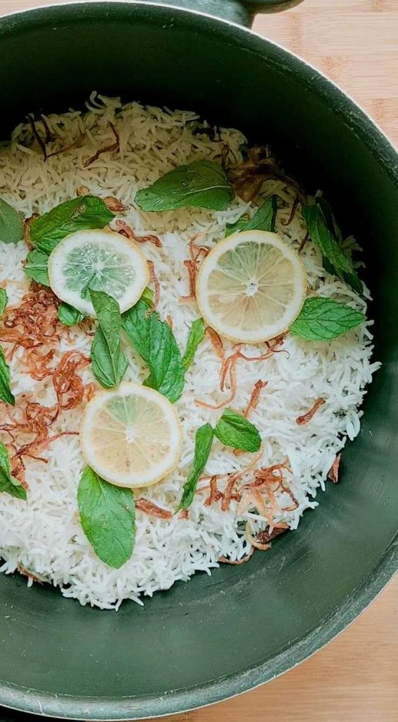 garnish layered on parboiled white rice in a pot